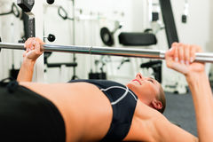 Woman in gym exercising with barbell Royalty Free Stock Photo