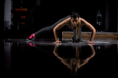 Woman in a gym exercising, doing push ups. Dark background Royalty Free Stock Photos