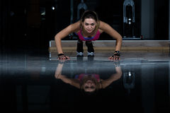Woman in a gym exercising, doing push ups. Dark background Royalty Free Stock Photography
