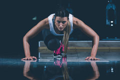 Woman in a gym exercising, doing push ups. Dark background Stock Photography