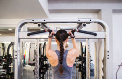 Woman in gym flexing back muscles on cable machine Royalty Free Stock Images