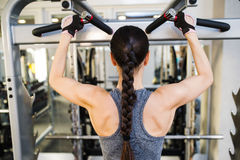 Woman in gym flexing back muscles on cable machine Royalty Free Stock Image