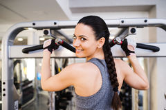 Woman in gym flexing back muscles on cable machine Royalty Free Stock Photography