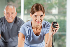 Woman in gym holding stopwatch Royalty Free Stock Images