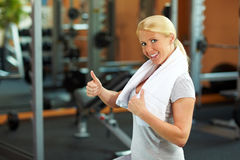 Woman in gym holding thumb up Royalty Free Stock Images