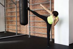 Woman in the gym kicks a foot on a punching bag royalty free stock photography