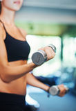 Woman in gym lifting bumbbells (soft focus) Royalty Free Stock Photo