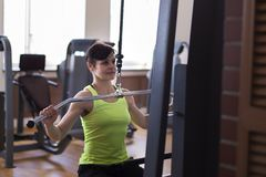 Woman in the gym, lifts the load royalty free stock photo