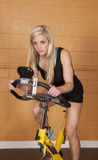 Woman gym looking on bike Royalty Free Stock Photography