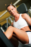 Woman in gym on machine Royalty Free Stock Image