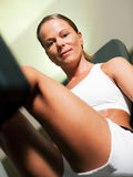 Woman in gym on machine Stock Images
