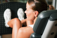 Woman in gym on machine Stock Photo