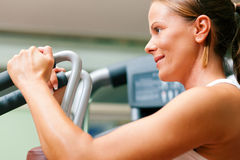 Woman in gym on machine exercising Royalty Free Stock Photos