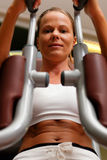 Woman in gym on machine exercising Royalty Free Stock Photo