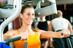 Woman in gym on machine exercising Stock Image