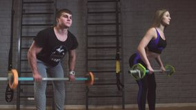 Woman in gym with personal fitness trainer exercising power gymnastics with a barbell stock video