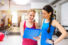 Woman in gym, personal trainer, consultiing plan on clipboard Royalty Free Stock Photo
