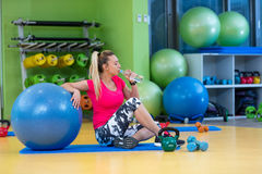 Woman at the gym with a pilates ball and water Royalty Free Stock Images