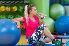 Woman at the gym with a pilates ball and water Stock Images