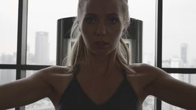 Woman in gym. Portrait of beautiful blonde woman at the gym exercising on a training machine. Gym with big windows. Healthy and active lifestyle. Slow motion stock video footage