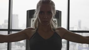 Woman in gym. Portrait of beautiful blonde woman at the gym exercising on a training machine. Gym with big windows. Healthy and active lifestyle. Slow motion stock video