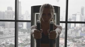 Woman in Gym. Portrait of beautiful blonde woman at the gym exercising on a training machine. Gym with big windows. Healthy and active lifestyle. Slow motion stock footage