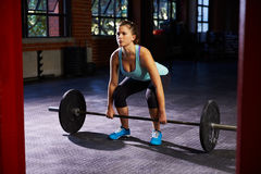 Woman In Gym Preparing To Lift Weights Stock Photography