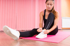 Woman in a gym putting on her trainers Stock Image