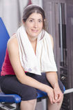 Woman in gym quadriceps machine. Resting with towel. Smiling and looking at teh view Stock Photo