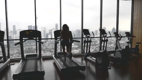 Woman in gym. Slow motion shot of attractive young woman running on a treadmill in fitness sport club with beautiful city view.Active lifestyle concept