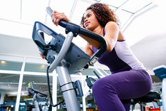 Woman in gym spinning on fitness bike Royalty Free Stock Photos