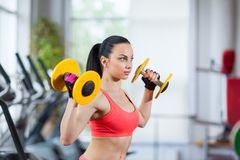Woman in gym sport exercising with dumbbells Stock Photo