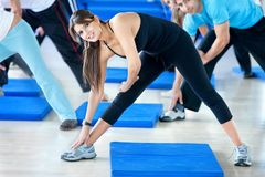 Woman at the gym stretching Stock Photo