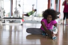 Woman in a gym stretching and warming up man in background worki Stock Images