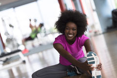 Woman in a gym stretching and warming up man in background worki Royalty Free Stock Photo