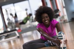 Woman in a gym stretching and warming up man in background worki Stock Image