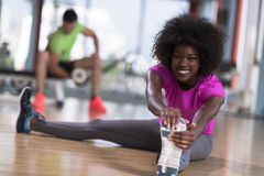 Woman in a gym stretching and warming up man in background worki Stock Photos
