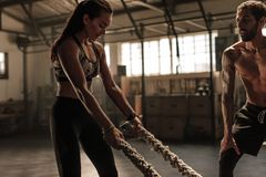 Woman at gym with trainer. Fitness women working out with battle ropes at gym. Female training with personal trainer in fitness club Royalty Free Stock Photography
