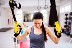 Woman in gym training arms with trx fitness strips. Fit attractive women in gym training arms with trx fitness strips Royalty Free Stock Photography
