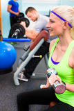 Woman in gym training - dumb bells Stock Image