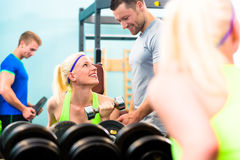 Woman in gym training with dumb bells. Woman with trainer in gym exercising with dumb bells Royalty Free Stock Photography