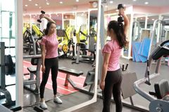 Asian chinese woman in gym lifting weights. Woman in gym try with dumbbells Stock Image