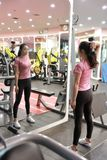 Asian chinese woman in gym lifting weights. Woman in gym try with dumbbells Stock Photo