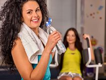 Woman in gym workout fitness equipment. Girl drink bottle water. Stock Photos