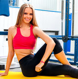 Woman in gym workout with fitness equipment. Girl relaxing after workout stretching lateral muscle on floor at gym. Female tired after training Royalty Free Stock Images
