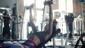 Woman on the gym. Young adult woman lifting weights in gymnasium stock video footage