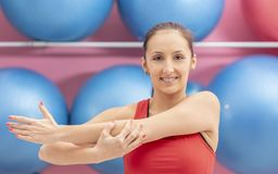 Woman in the Gym. Young woman doing stretching exercises in a gym Royalty Free Stock Photo