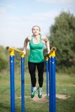 Woman gymnast exercising on parallel bars Royalty Free Stock Photo