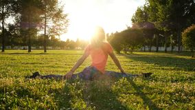 Girl gymnast sits on a splits on the grass in a city park on the nature and makes turns in the back and stretching stock photos