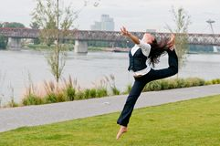 Woman in gymnastics jump outdoors Royalty Free Stock Images